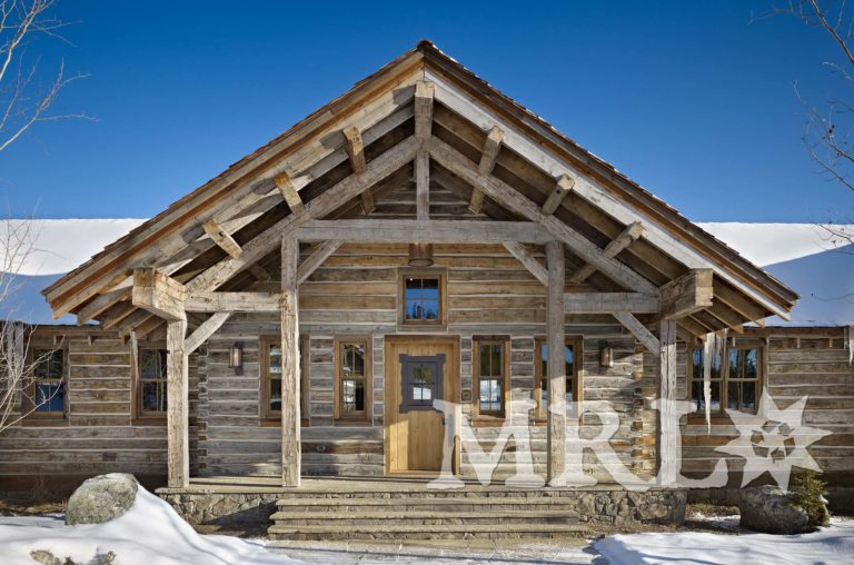 A photo of our reclaimed hand hewn timbers and slabs used to clad posts, coffer ceilings, frame entrances, and side the exterior along with corral board accents featured throughout the Ranch 1 project.