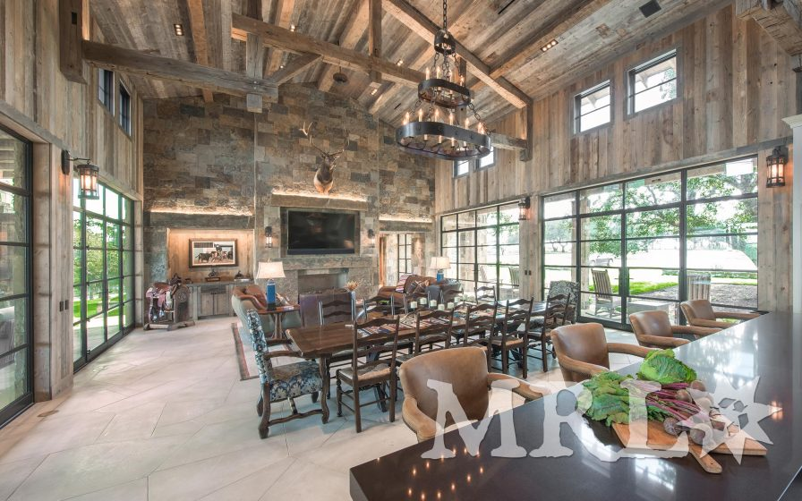 A photo of reclaimed corral board paneling, siding, and doors along with hand hewn slab paneling and timbers as featured throughout the Weatherford project.