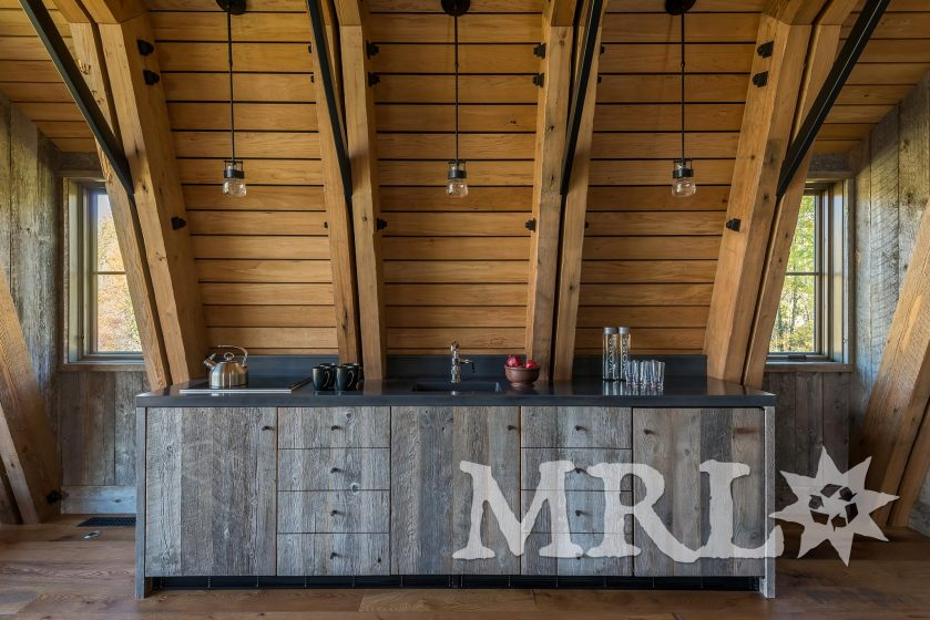 A photo of reclaimed western hemlock for structural trusses, Montana corral board paneling and our custom rafter stock siding in The Barn project.